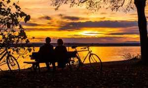 lago tramonto coppia bici